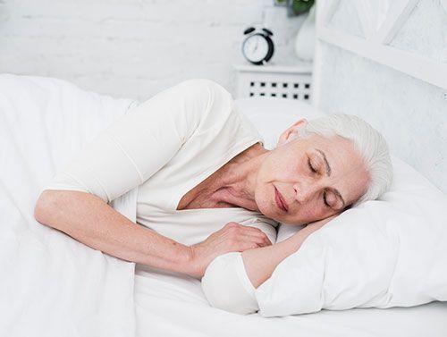 Mujer mayor durmiendo de lado con colchón y almohada