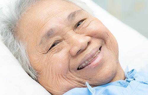 Mujer anciana enferma sonriendo en la cama