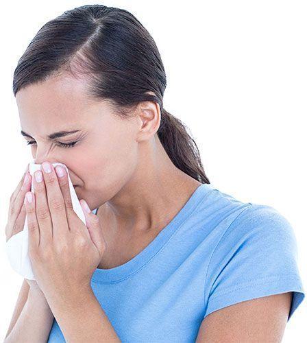 Chica morena con alergia limpiándose la nariz