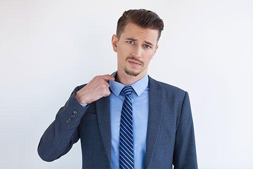 Chico joven con traje y corbata sudando con calor