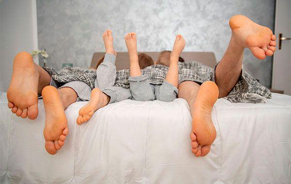 Familia tumbada en la cama con los pies descalzos fuera